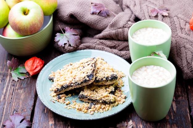 Due tazze di caffè o cioccolata calda con marshmallow vicino a maglia coperta e torta