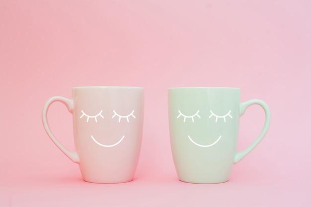 Due tazze di caffè stanno insieme per essere a forma di cuore su sfondo rosa con faccina sorridente