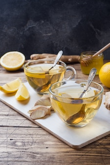 Due tazze di tisana naturale allo zenzero limone e miele su una superficie di legno.