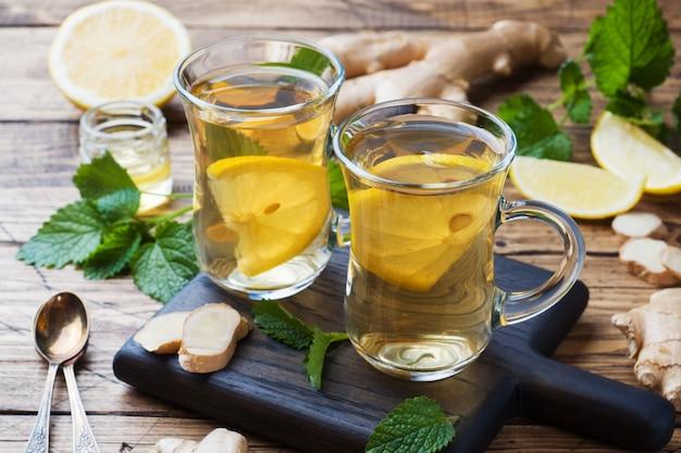 Due tazze di tisana naturale zenzero limone menta e miele su una superficie di legno.