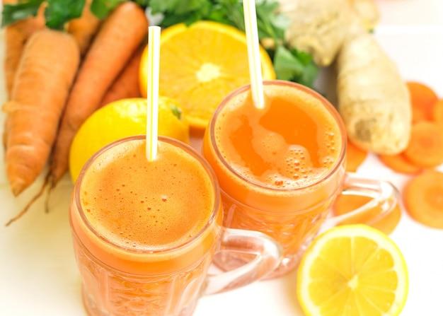 Due tazze di vetro con un frullato di carote e cannucce da cocktail.