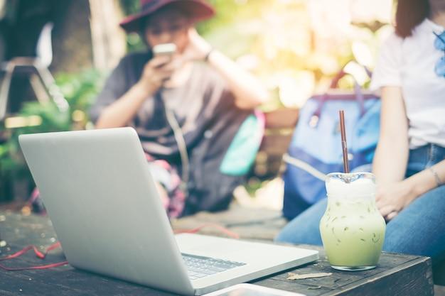 Due tazze e computer portatili di belle ragazze in caffè di estate