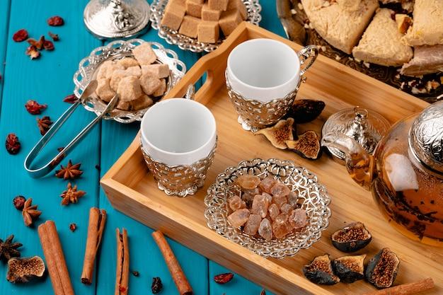 Due tazze vuote su un vassoio di legno con zollette di zucchero e baklava turca sulla tavola di legno blu decorata con bastoncini di cannella