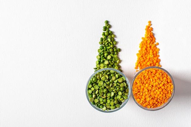 Due tipi di legumi, splendidamente disposti in tazze e su bianco - piselli e lenticchie arancioni. vista dall'alto. copia spazio.