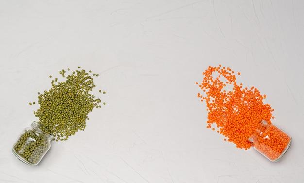 Due tipi di lenticchie semole di lenticchie verdi e arancioni per vegani in barattoli di vetro