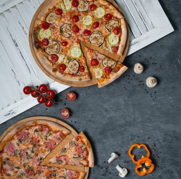 Due tipi di pizza con ingredienti misti