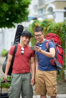 Due turisti asiatici maschii che esaminano smartphone in via della città