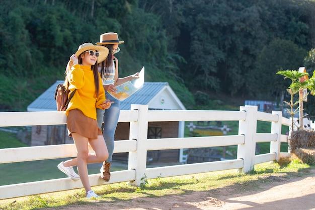 Due turisti femminili tengono una mappa per trovare posti.