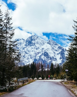 Due turisti in piedi sulla strada vicino alla montagna innevata