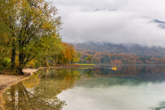 Due turisti irriconoscibili fanno una gita in canoa intorno al suggestivo lago di bohinj in una bella giornata d'autunno. i viaggiatori vanno in kayak verso la riva e le case vacanza si nascondono tra gli alberi cambiando colore