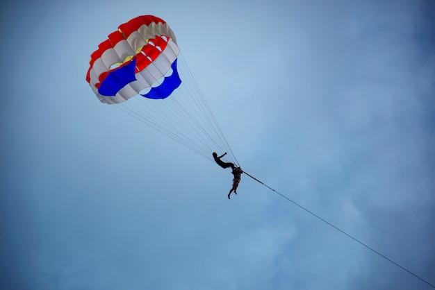 Due turisti stanno giocando il parasailing nel cielo durante l'estate.