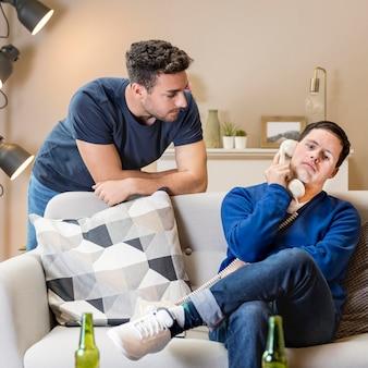Due uomini a casa che posano con il telefono