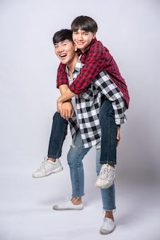 Due uomini amorevoli indossavano camicie a righe e cavalcavano la schiena.