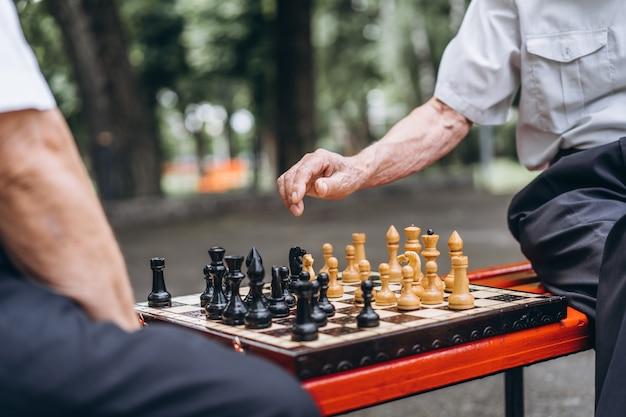 Due uomini anziani che giocano a scacchi sulla panchina all'aperto nel parco