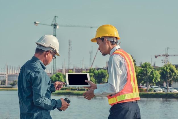 Due uomini asiatici parlando progetto di costruzione di affari all'aperto sul sito immobiliare, project manager, ingegnere di progetto