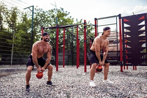 Due uomini atletici che risolvono con un kettlebell all'iarda della palestra della via.