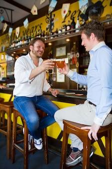 Due uomini che bevono birra al bar