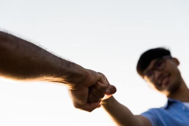 Due uomini che danno urto di pugno mostrando unità e lavoro di squadra. amicizia, concetto di partnership.