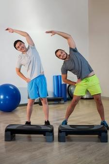 Due uomini che fanno esercizio aerobico con stepper
