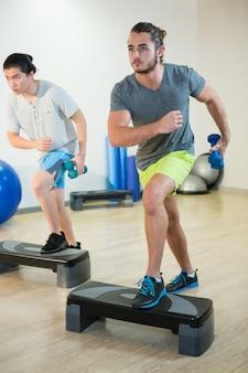 Due uomini che fanno esercizio aerobico step con manubri su stepper