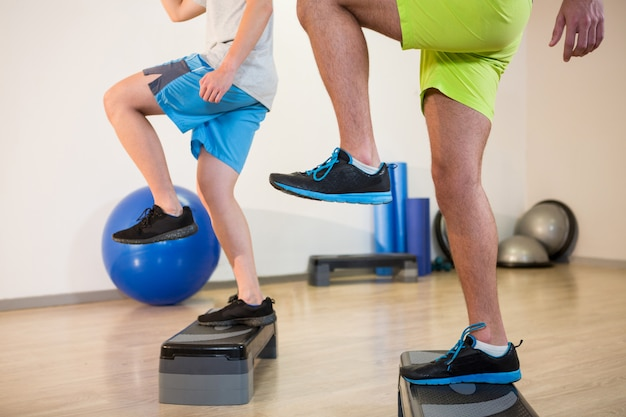 Due uomini che fanno esercizio aerobico step su stepper