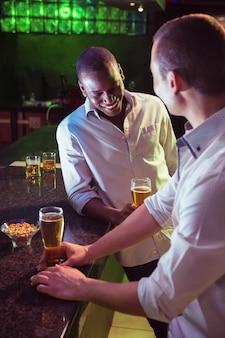 Due uomini che mangiano birra al bancone del bar nel bar