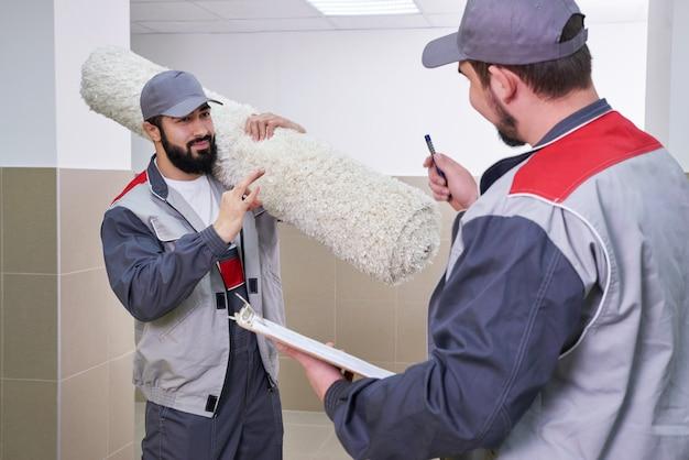 Due uomini che portano via un grande tappeto per il servizio di pulizia