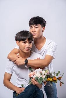 Due uomini che si amano si abbracciano da dietro l'altro.