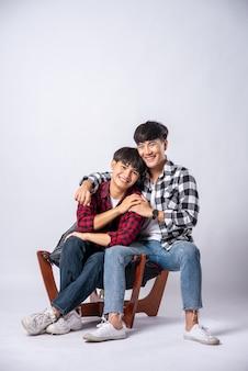 Due uomini che si amano si abbracciano e si siedono su una sedia.