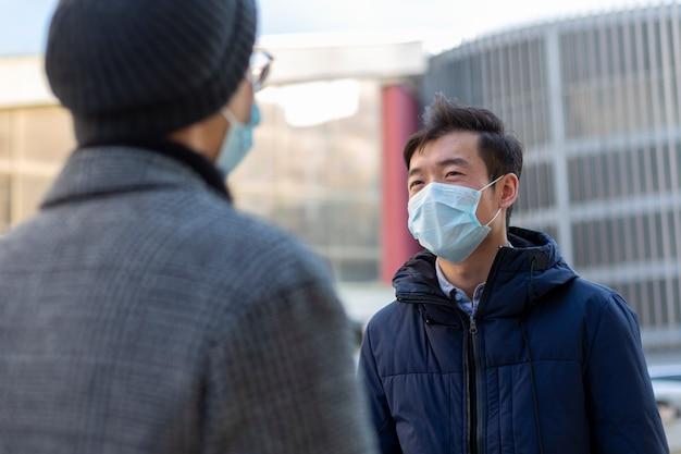 Due uomini cinesi in maschere protettive mediche contro la conversazione covid-2019