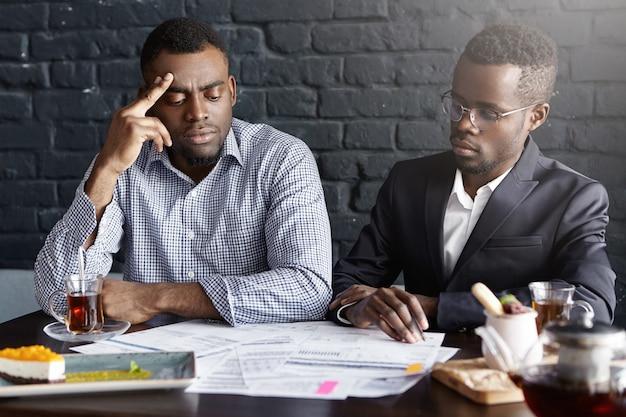 Due uomini d'affari afro-americani che firmano il contratto durante la riunione d'affari alla scrivania