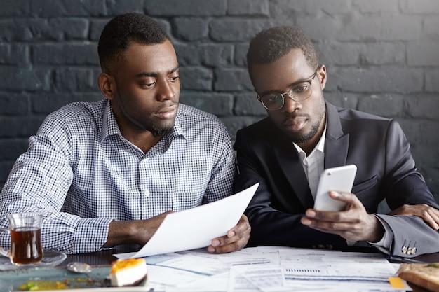 Due uomini d'affari afroamericani fiduciosi e seri si sono concentrati sul lavoro di ufficio