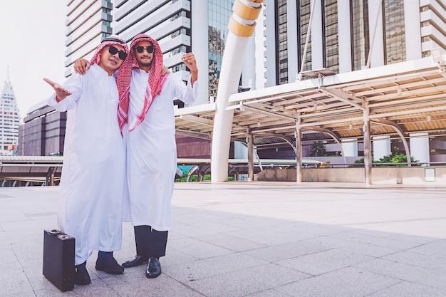Due uomini d'affari arabi in piedi alzando entrambe le mani in città
