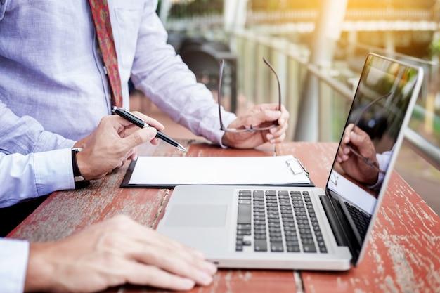 Due uomini d'affari che discutono le attività di pianificazione con il computer portatile che si siede sul tavolo esterno