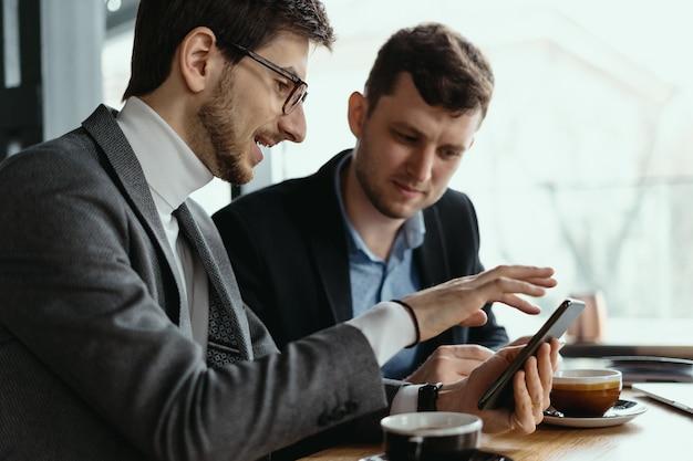 Due uomini d'affari che hanno una conversazione usando uno smartphone