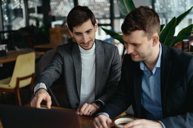 Due uomini d'affari che indicano lo schermo del laptop mentre discutono