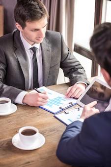 Due uomini d'affari che lavorano durante un pranzo di lavoro.