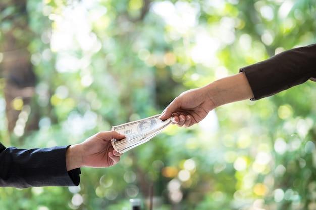 Due uomini d'affari che suggellano l'affare con una stretta di mano e ricevono una tangente.