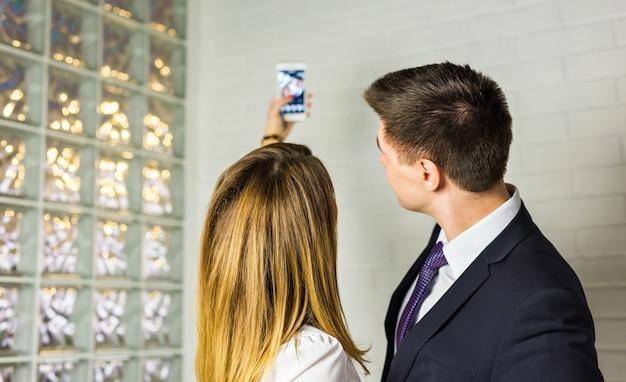 Due uomini d'affari di successo prendendo un selfie felice in ufficio.