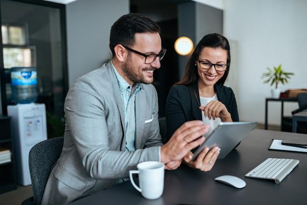 Due uomini d'affari eleganti sorridendo e guardando la tavoletta digitale.