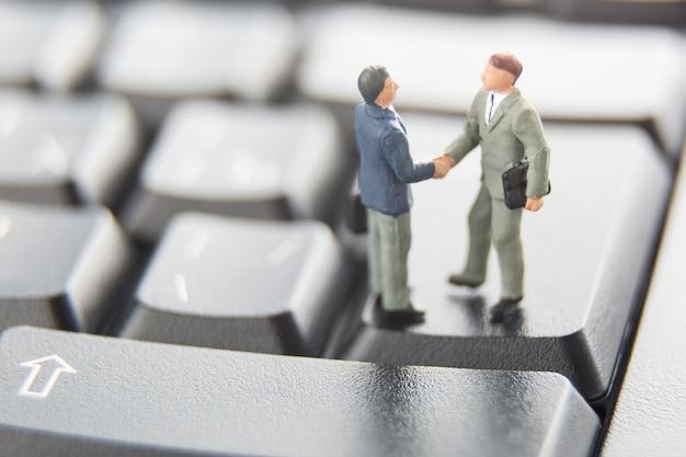 Due uomini d'affari in miniatura si stringono la mano in piedi sui tasti di una tastiera nera.