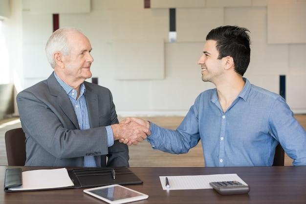 Due uomini d'affari positivi che agitano le mani