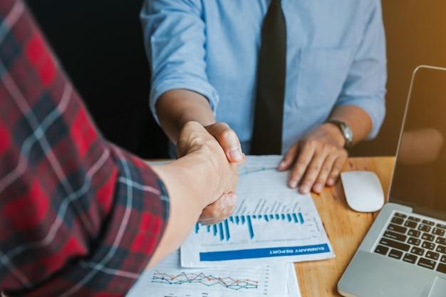 Due uomini d'affari si stringono la mano durante una riunione in ufficio