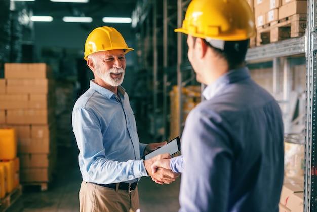 Due uomini d'affari si stringono la mano per affari di successo, mentre in piedi in magazzino.