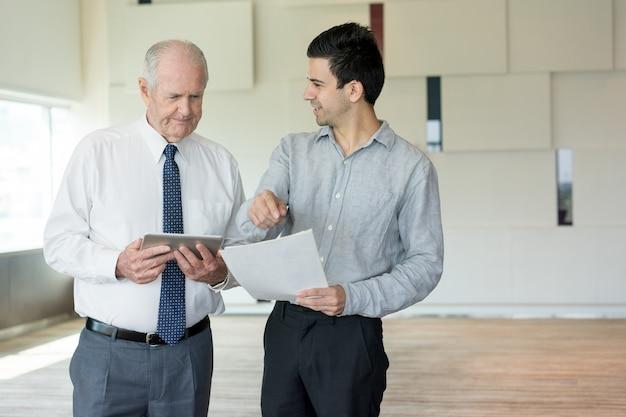 Due uomini d'affari soddisfatti che discutono documento