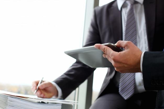Due uomini d'affari stanno guardando e prendendo appunti