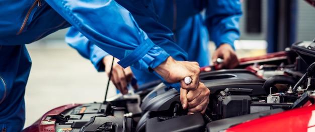 Due uomini del meccanico che riparano i danni alla macchina nel negozio di riparazioni auto