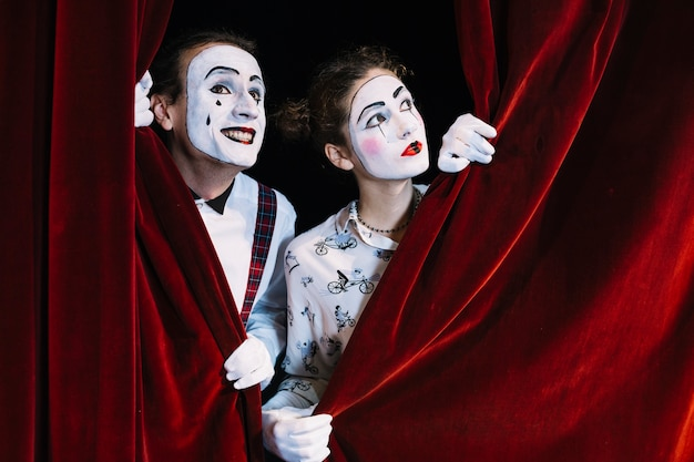 Due uomini e donne mimo artista guardando attraverso la tenda rossa