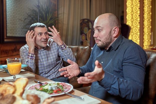 Due uomini in un ristorante che discutono durante il pranzo