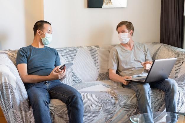 Due uomini multietnici con maschera come amici che usano la tecnologia e parlano in quarantena a casa